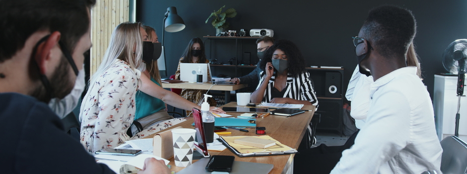 Office safety during COVID-19. Young multiethnic serious business people work together at meeting wearing face masks.