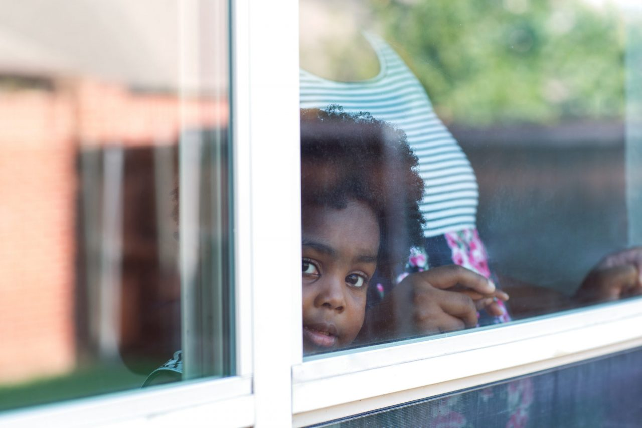 Young African American little girl looking out the window.