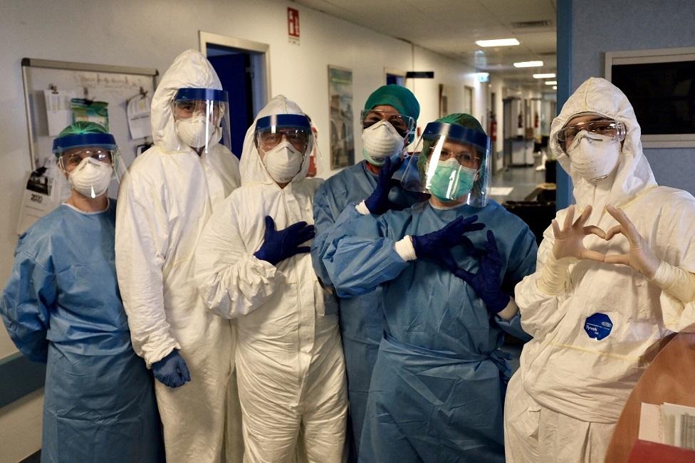 com-jalecos-e-itens-de-protecao-profissionais-de-saude-fazem-sinal-de-coracao-com-as-maos-de-dentro-de-hospital-20032020090439038